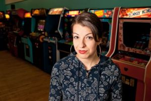 Anita Sarkeesian poses in front of arcade games she may or may not have played